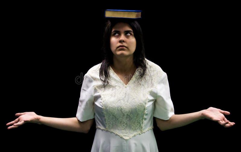 Latina som är tonårig med boken på huvudet arkivbilder