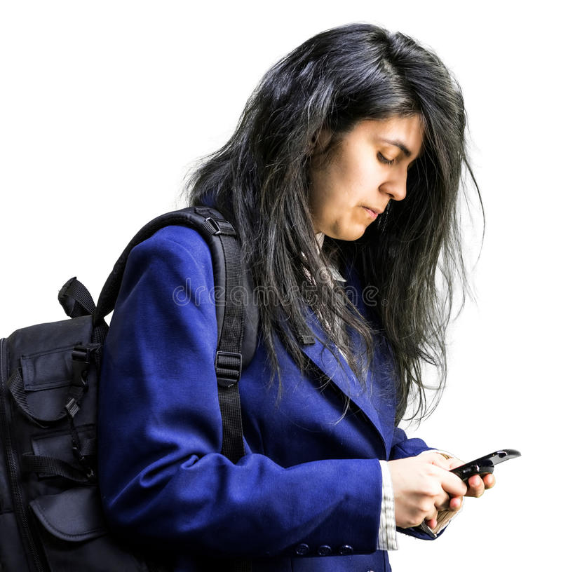 Latina teen girl looking down at cell phone. Side shot of latina teen girl with a backpck on looking down at cell phone royalty free stock images