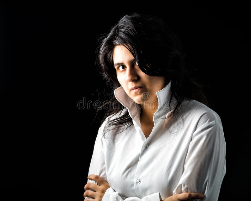 Latina teen in white on black backdrop. Latina teen in white long sleeved shirt standing in front of black backdrop with arms crossed and looking at the camera stock photo