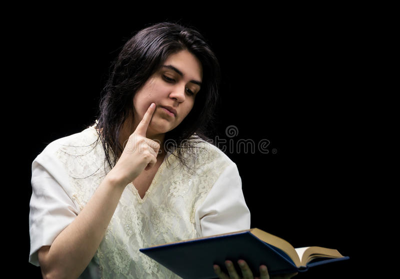 Latina teen in white holding a book on black background. Latina teen in white dress holding a blue book with gold edging, holding a finger to her cheek and royalty free stock photography