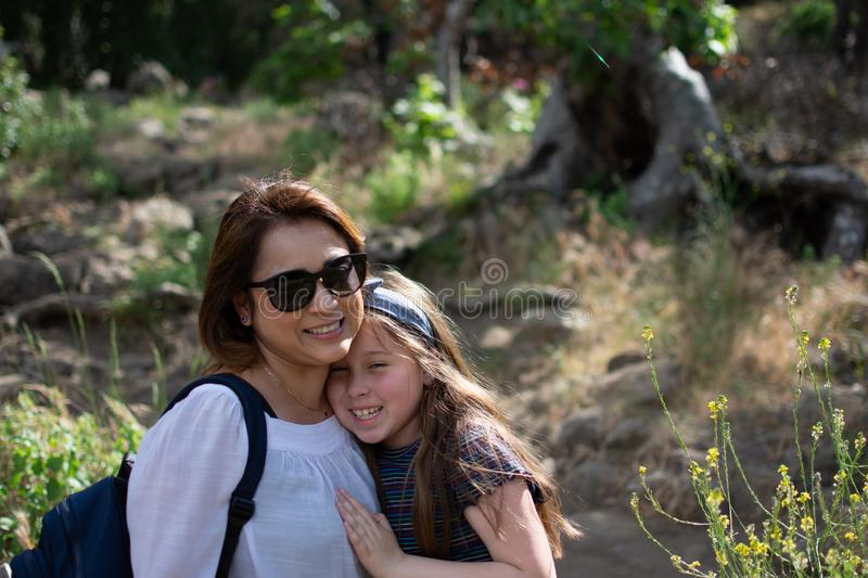 Latina Woman and daughter smiling together while standing in front of woods at a park stock photography