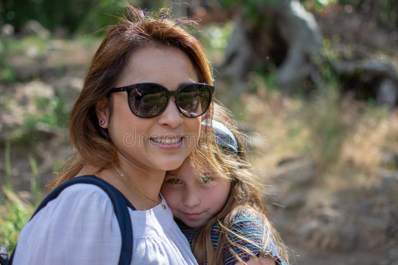 Latina Woman and daughter smiling together while standing in front of woods at a park stock image