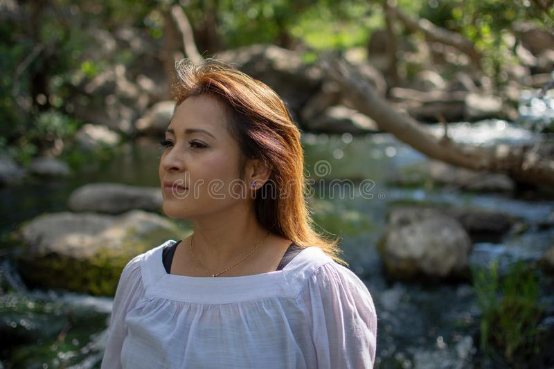Latina woman with serious expression standing in the shade with glowing hair in a stream with waterfalls in the background stock photography