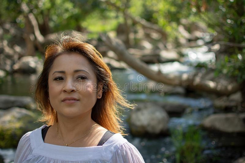 Latina woman with serious expression standing in the shade with glowing hair in a stream with waterfalls in the background stock photo