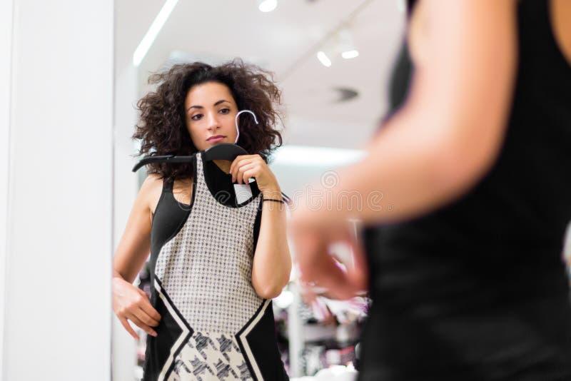 Latina Woman shopping fashion dress in store stock photo