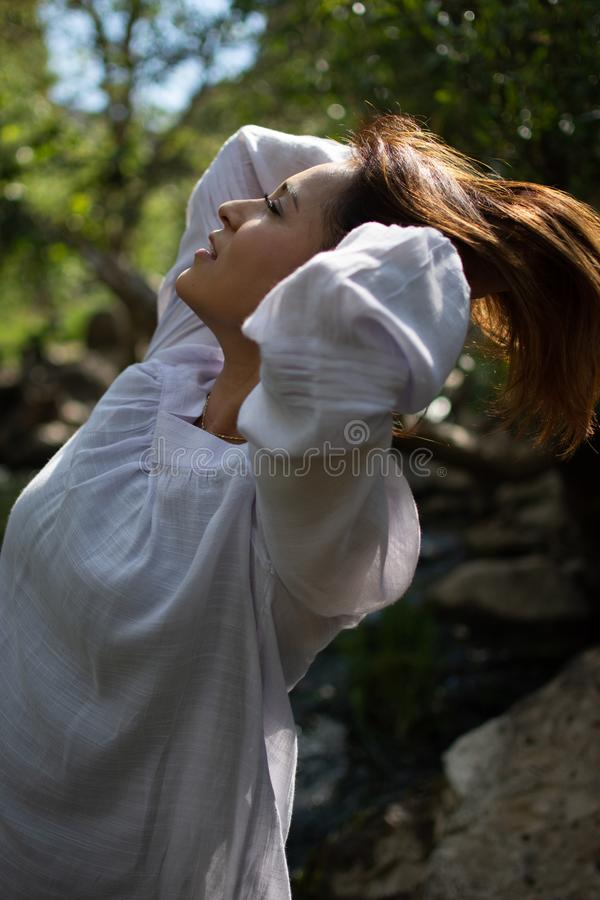 Latina woman throwing her hair back with her hair in the sun in front of woods and a stream in the shade royalty free stock images