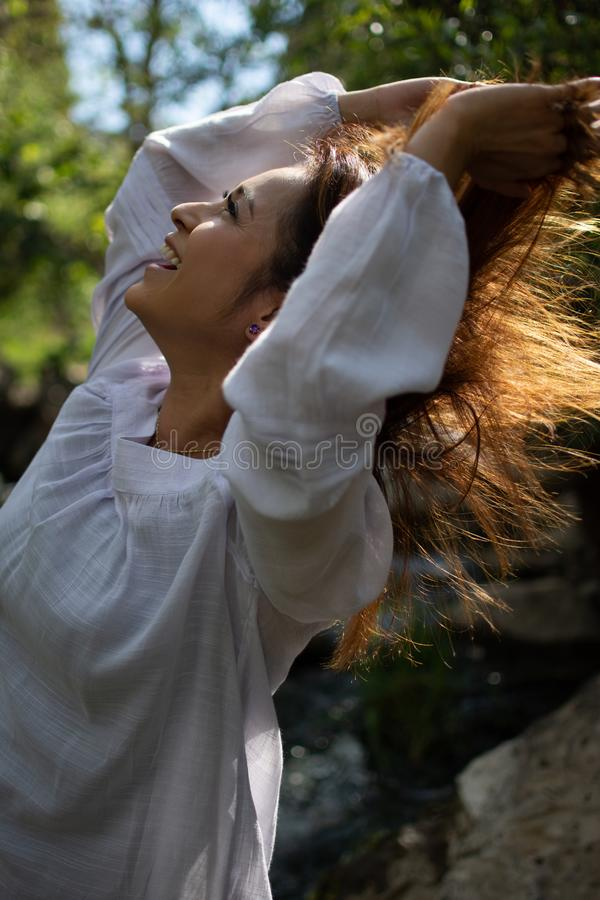 Latina woman throwing her hair back with her hair in the sun in front of woods and a stream in the shade royalty free stock photo