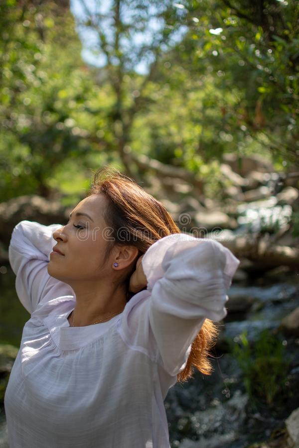 Latina woman throwing her hair back with her hair in the sun in front of woods and a stream in the shade royalty free stock photography