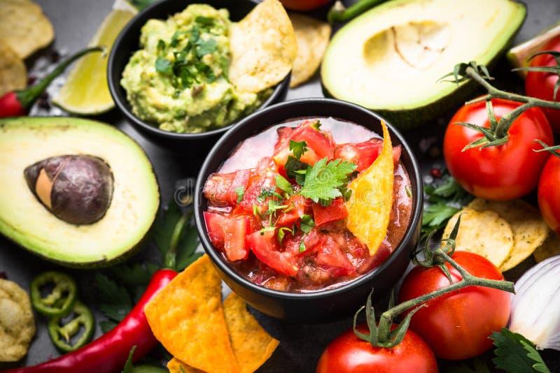 Latinamerican food party sauce guacamole, salsa, chips and ingre. Latinamerican mexican food party sauce guacamole, salsa, chips and ingredients on black table royalty free stock photo