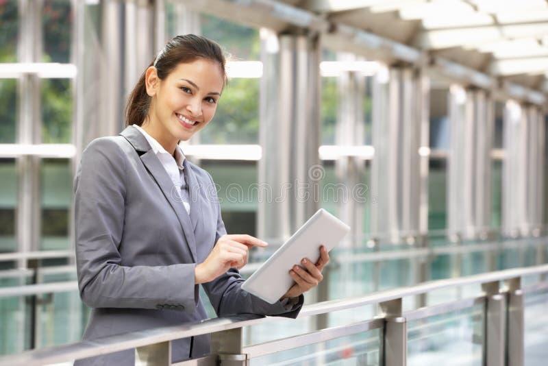 Latinamerikansk affärskvinna som fungerar på Tabletdatoren arkivbilder