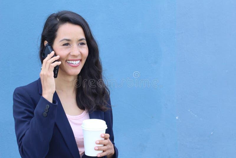 Latinamerikansk affärskvinnakontorsarbetare som meddelar med mobiltelefonen på kaffeavbrott royaltyfri bild