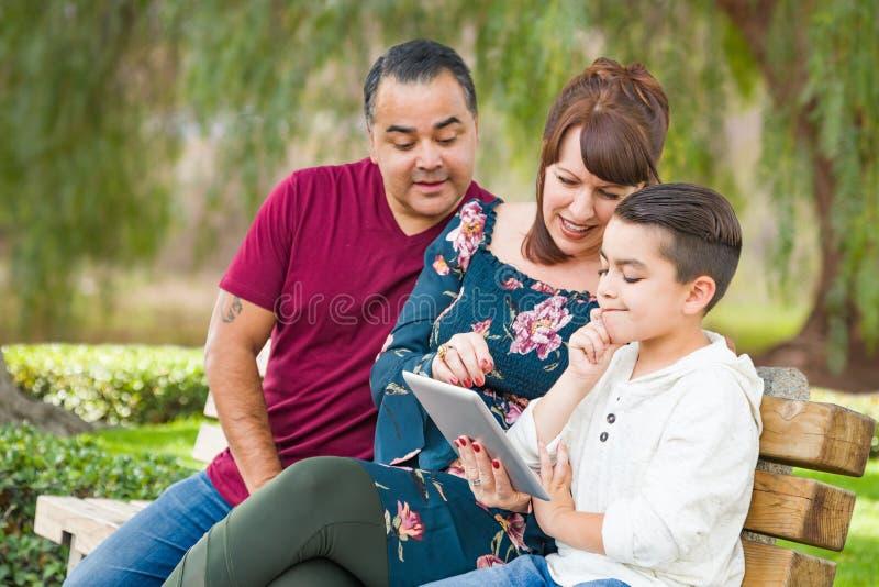 Latinamerikansk fader och Caucasian moder som utomhus använder datorminnestavlan med sonen för blandat lopp royaltyfri bild