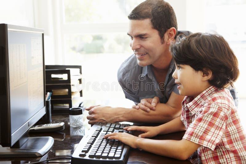 Latinamerikansk fader och son som hemma använder datoren arkivfoton