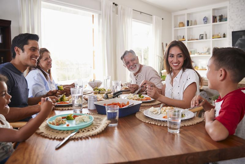 Latinamerikansk familj för tre utveckling som sitter på tabellen som äter matställen arkivbilder
