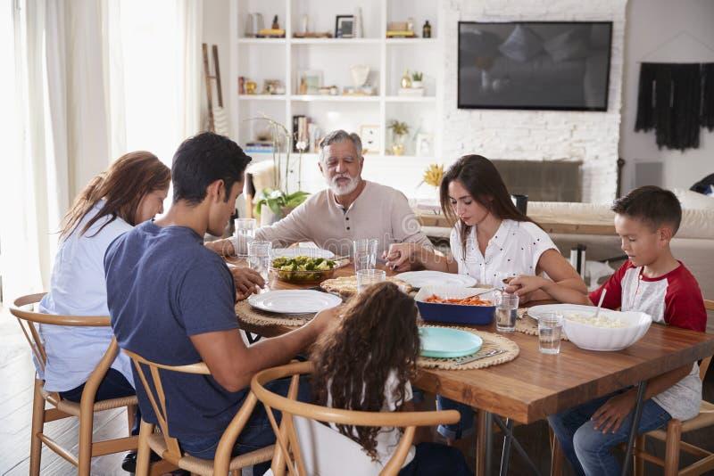 Latinamerikansk familj för tre utveckling som sitter på tabellen som rymmer händer och säger nåd för matställe royaltyfri foto