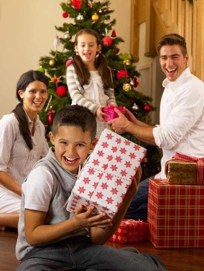 Latinamerikansk familj hemma runt om jultree arkivbilder
