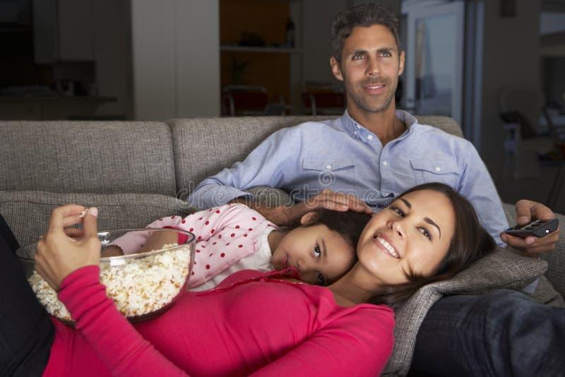 Latinamerikansk familj på Sofa Watching TV och ätapopcorn arkivbilder