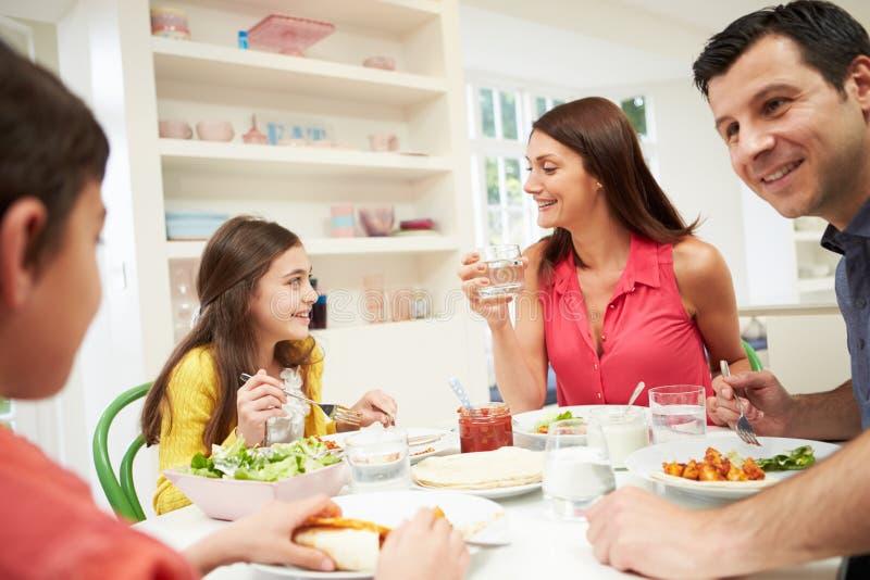 Latinamerikansk familj på tabellen som tillsammans äter mål royaltyfria bilder