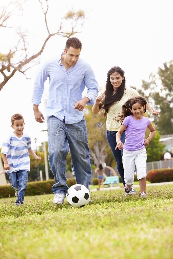 Latinamerikansk familj som spelar fotboll tillsammans arkivfoto