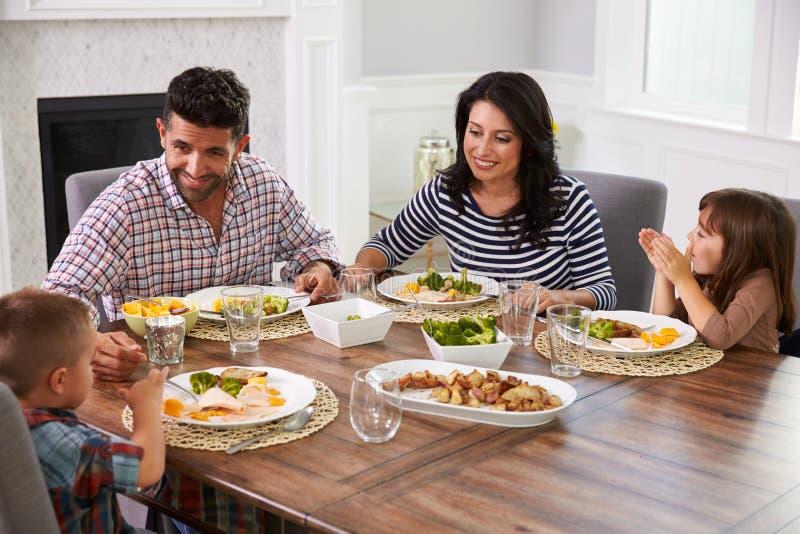 Latinamerikansk familj som tycker om mål på tabellen fotografering för bildbyråer