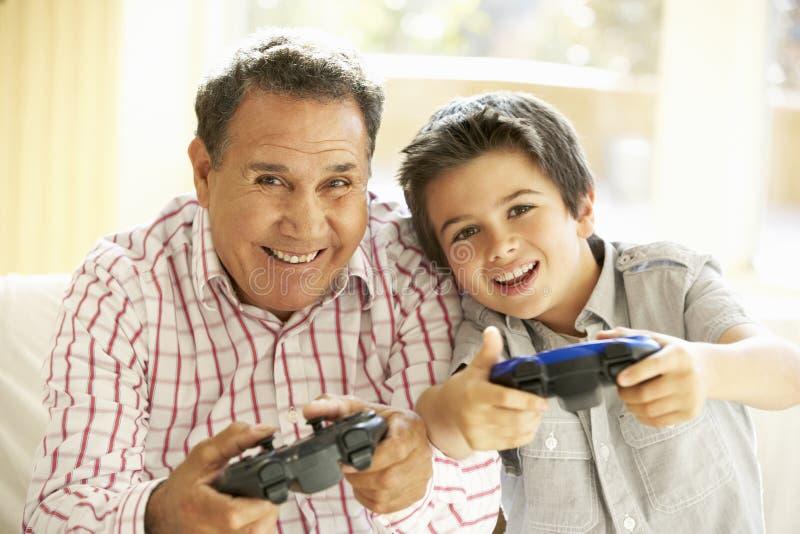 Latinamerikansk farfar och sonson som hemma spelar videospelet royaltyfri foto