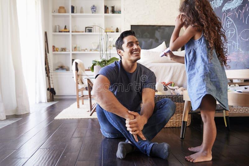 Latinamerikansk farsa som sitter på golvet i vardagsrum som lyssnar hans unga dotter, sidosikt royaltyfri fotografi