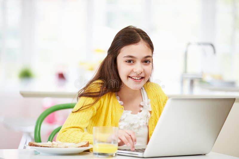 Latinamerikansk flicka som använder bärbara datorn som äter frukosten royaltyfria bilder