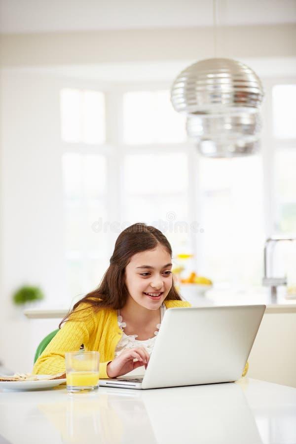Latinamerikansk flicka som använder bärbara datorn som äter frukosten royaltyfria foton