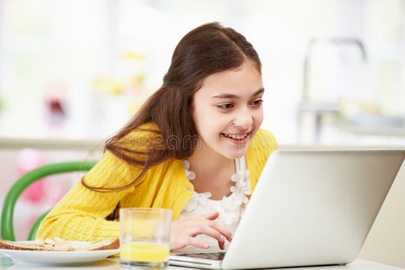 Latinamerikansk flicka som använder bärbara datorn som äter frukosten arkivfoton