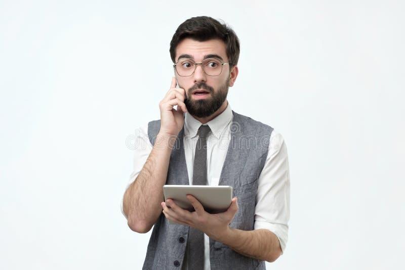 Latinamerikansk grabb med skägget som talar på en mobiltelefon som försöker att finna lösningen från finansiella problem royaltyfri foto