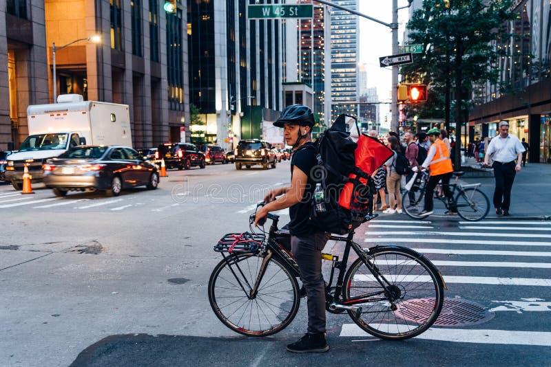 Latinamerikansk kurir på cykeln i övergångsställe i New York City royaltyfria bilder