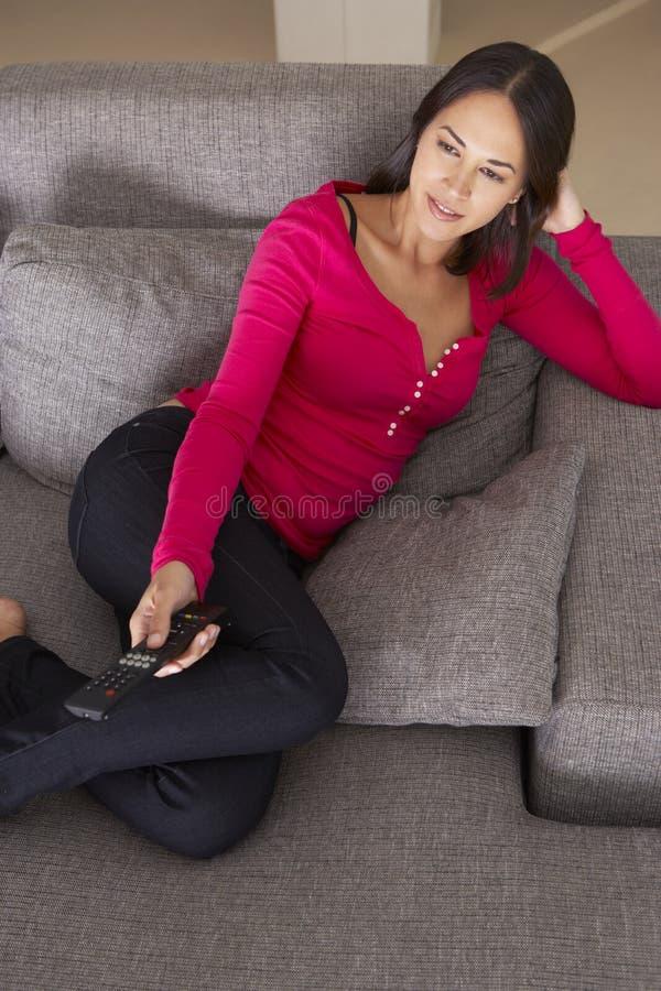 Latinamerikansk kvinna på Sofa Watching TV royaltyfria bilder