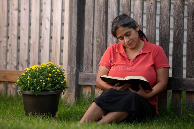 Latinamerikansk kvinna som läser hennes bibel vid blomkrukan royaltyfri foto