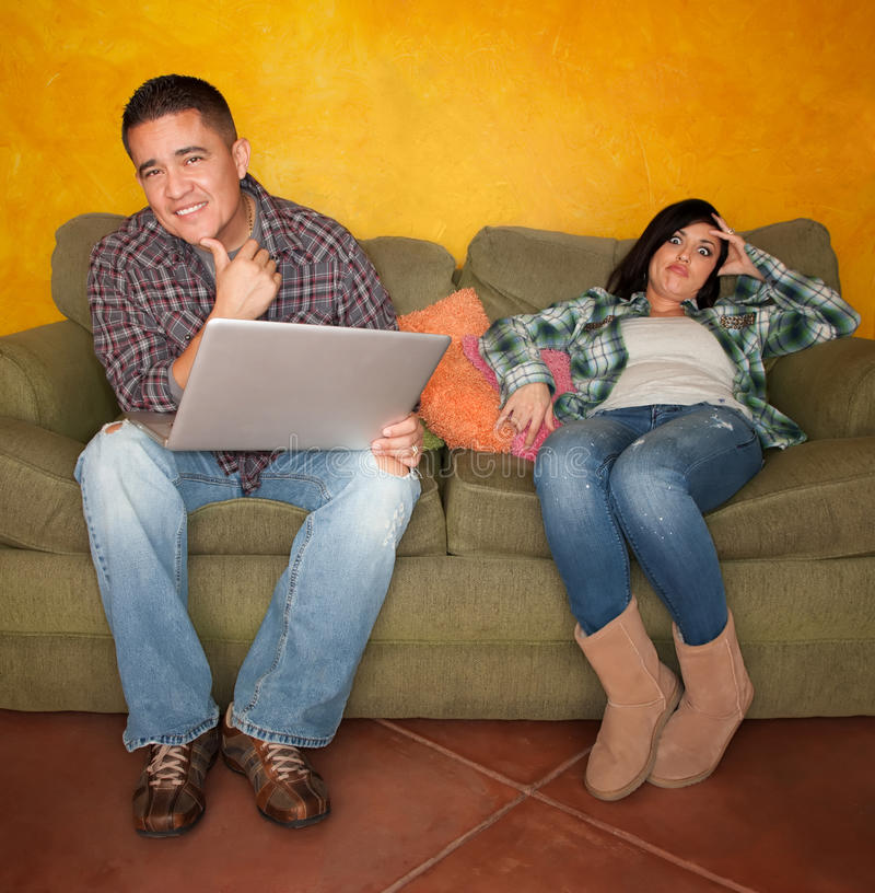latinamerikansk man för uttråkad dator som reagerar till kvinnan arkivfoton