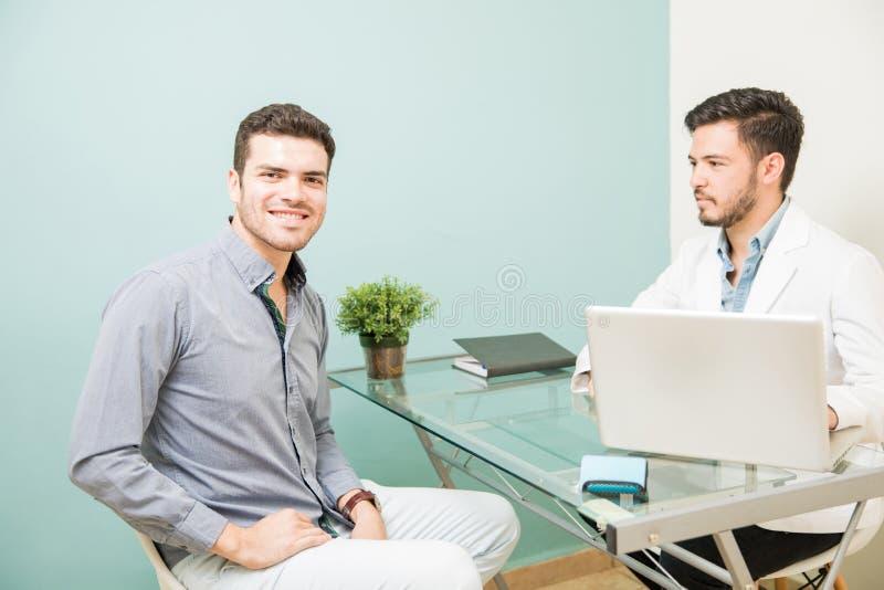 Latinamerikansk man som besöker hans näringsfysiolog royaltyfria foton