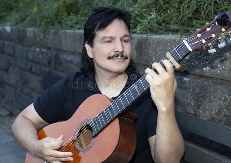 Latinamerikansk man som spelar den akustiska gitarren utomhus royaltyfri bild