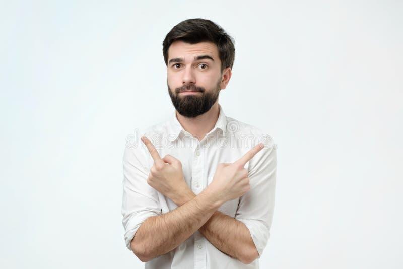 Latinamerikansk man som väljer mellan begreppet för två alternativ Han pekar till olika sidor vid hans fingrar royaltyfri foto