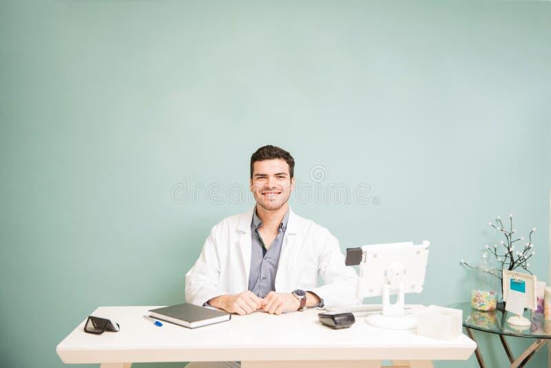 Latinamerikansk manlig terapeut i ett främre skrivbord arkivfoto