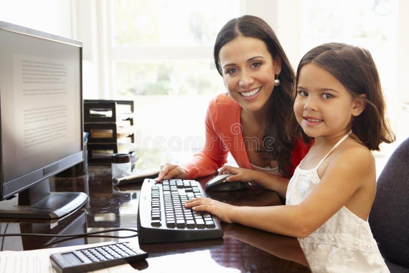Latinamerikansk moder och dotter som hemma använder datoren arkivfoton