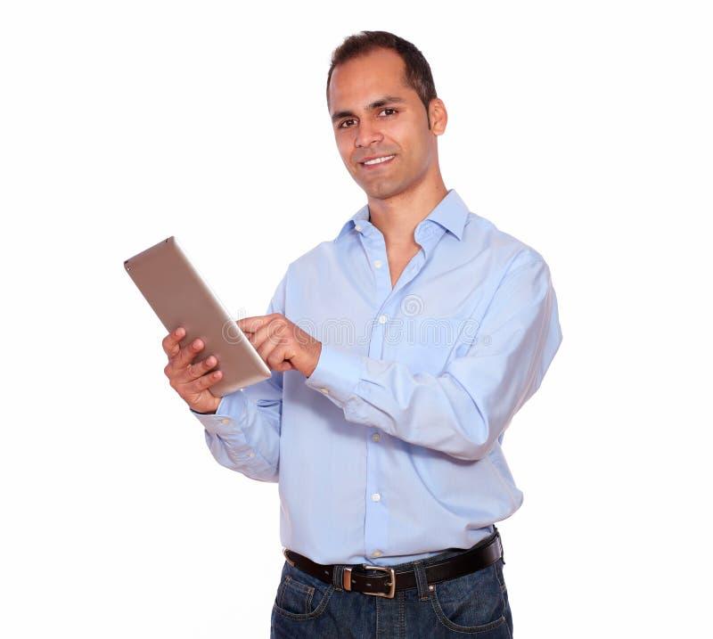 Latinamerikansk vuxen man som använder hans minnestavlaPC arkivfoto