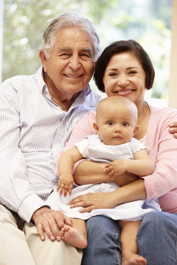Latinamerikanska morföräldrar hemma med barnbarnet fotografering för bildbyråer