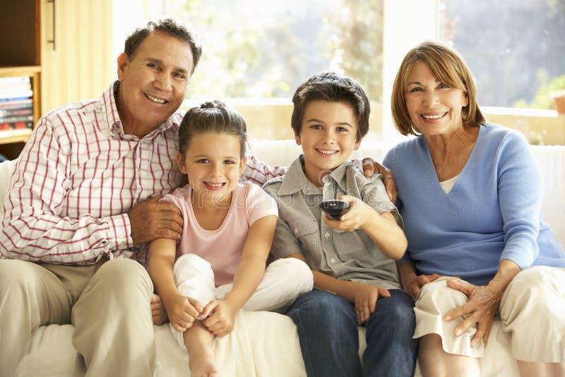 Latinamerikanska morföräldrar med barnbarn som håller ögonen på TV på Sofa At Home arkivfoton