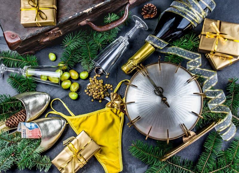 LATINAMERIKANSKA OCH SPANSKA TRADITIONER FÖR NYTT ÅR tom resväska, linssked, gul inre kläder, guld- cirkel in royaltyfria bilder