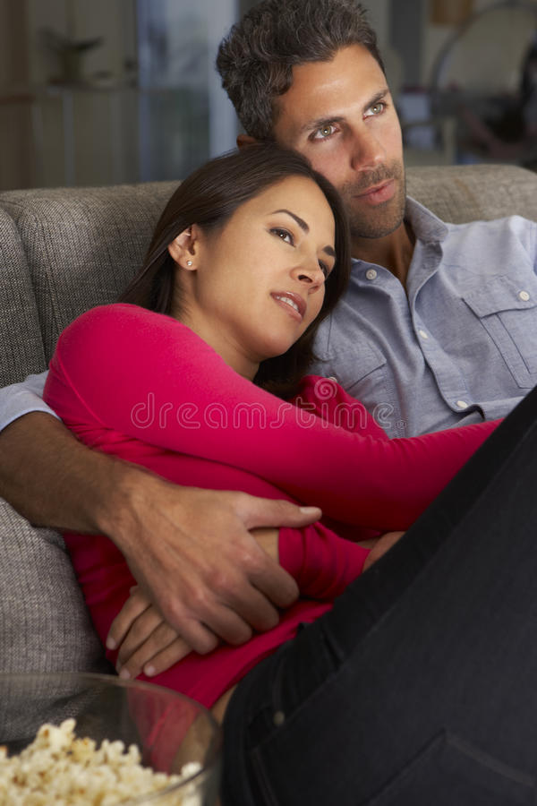 Latinamerikanska par på Sofa Watching TV och ätapopcorn royaltyfri fotografi