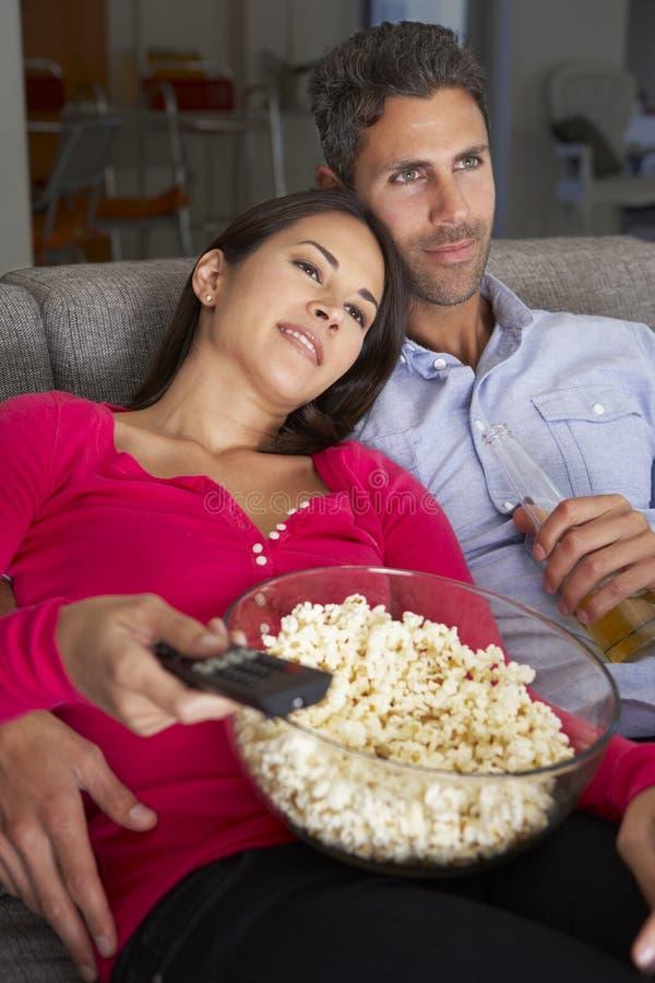 Latinamerikanska par på Sofa Watching TV och ätapopcorn arkivfoto