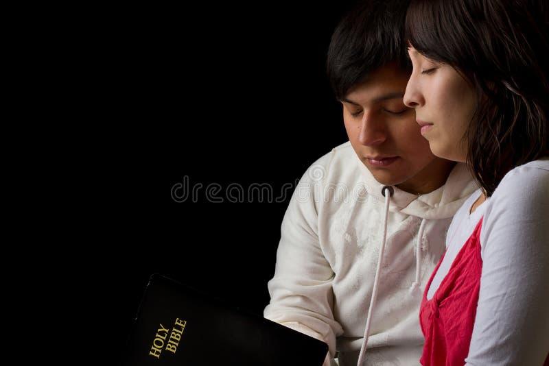 Latinamerikanska par som studerar bibeln och be arkivfoton