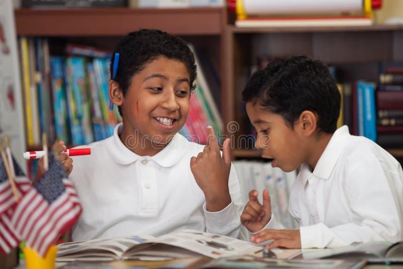 Latinamerikanska pojkar i denskola inställningen som har gyckel med böcker royaltyfria foton