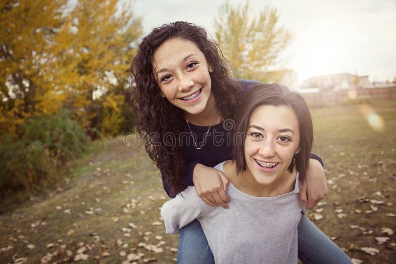 Latinamerikanska tonårs- flickor som har gyckel tillsammans utomhus royaltyfri foto