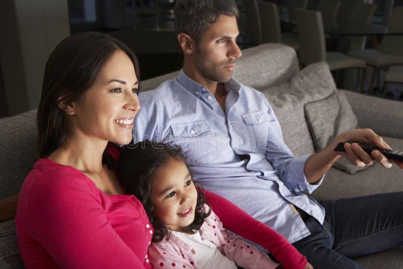 Latinamerikanskt familjsammanträde på Sofa And Watching TV arkivfoton