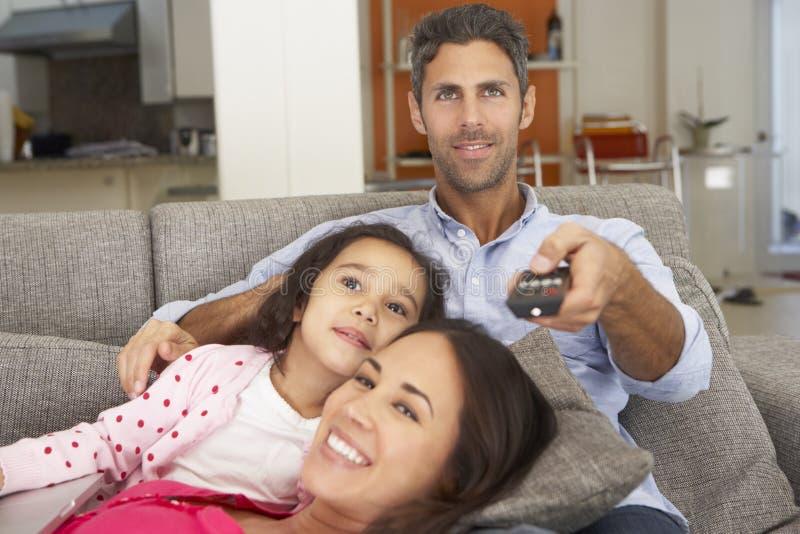 Latinamerikanskt familjsammanträde på Sofa And Watching TV royaltyfri bild